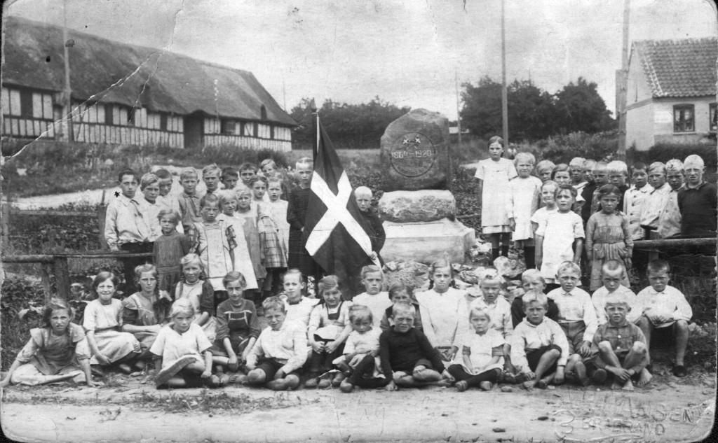 1920. Byens børn bliver fotograferet ved den nye mindesten. Siden blev der holdt fest ved vandmøllen. Til venstre ses tvillingegården Borum Højgård og den unavngivne gård, der senere fik navnet Storkesiggård. Til højre huset Bysvinget 2.