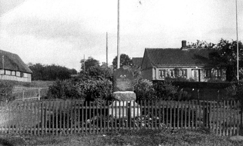 1939. Omkring mindestenen står et lille anlæg indrammet af stakit. Alt ånder fred og idyl.