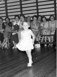Birgit til danseskole i Borum Forsamlingshus 1960. Bemærk ribberne i salen på gavlvæggen mod vest og de cigaretrygende mødre i baggrunden